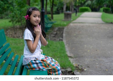 Asian child cute girl Sit on a green long chair in the garden
