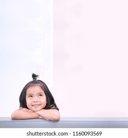 Asian child cute or kid girl and student thinking with looking on top for new idea and happy fun or smile on sofa at kindergarten or nursery and child hospital or school with space on brown