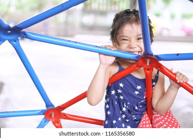 Asian child cute or kid girl smile playing climb old colorful cage and happy fun or cheerful enjoy on holiday relax with exercise at playground or amusement public park and nursery kindergarten school
