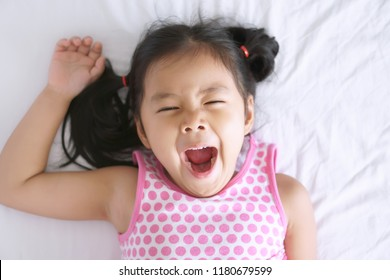 Asian child cute or kid girl sleep yawn and open mouth with stretch oneself after wake up late and sleepy in the morning on white bed in bedroom for relax on holiday with wear pink dress