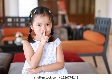 Asian child cute or kid girl smile with laugh squat and forefinger close mouth for tell quietly shh or stop silence and secret surprise with play hide and seek at library at school or reception room