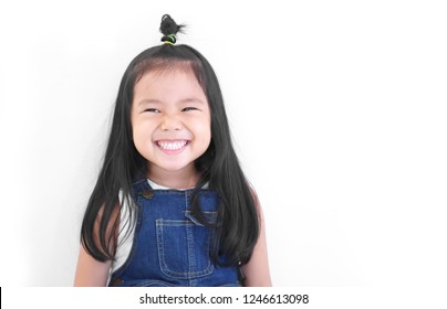 Asian child cute or kid girl and kindergarten student happy smile white teeth and laugh thinking for new idea with wear dungarees jean at dental or pre school on white background with space isolated