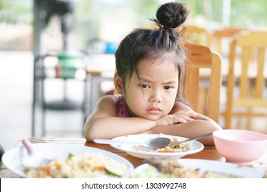 Asian child cute or kid girl anorexia or sad and bored food or boredom with sleepy vacant and prop up or hand to cheek on wood table for breakfast or lunch eating at restaurant on preschool