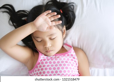 Asian child cute or kid girl sleep headache sick and fever with pale from virus and hand to the forehead with sad on white pillow and bed with wear pink dress at home or children hospital