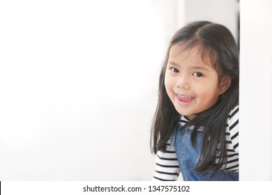 Asian child cute or kid girl playing peekaboo or hide and seek with sneaked or dodge behind the post and happy smiling white teeth or cheerful at public park or playground on relax holiday with space