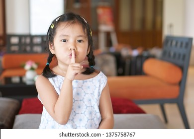 Asian child cute or kid girl squat and forefinger close mouth for tell quietly shh or stop silence and secret surprise with play hide and seek in library room at school or reception room