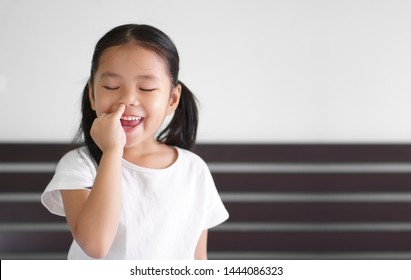 Asian child cute or kid girl enjoy nose picking or picky by finger with eat snot and smiling happy with close eye on preschool or 5 years old and wear white t-shirt with copy space