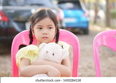 Asian child cute or kid girl pigtail sad with miss and lonely with hug teddy bear doll to lovely toy on street or city park with car and vacant sit on pink chair
