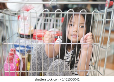 Asian child cute or kid girl happy smiling and sit in supermarket cart for food product sale and buy or housewares shopping with enjoy funny in super market at department store on holiday relax