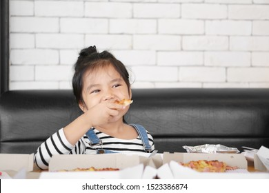 Asian child cute or kid girl enjoy eating hawaiian pizza or italian food in box with thick cheese and crisp thin to hungry for happy breakfast or lunch at cafe restaurant or home on table and sofa
