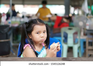 Asian child cute or kid girl hungry and enjoy eating corn boil for vegetable food or fruit snack with fiber vitamin to health diet and happy smiling in fresh market on street travel and relax