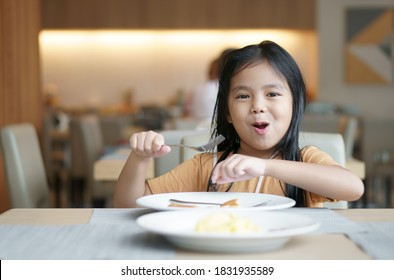 Asian child cute or kid girl smile holding fork to enjoy eating delicious food to hungry on white dish and table with happy for lunch or breakfast and appetizing in morning at restaurant or food court