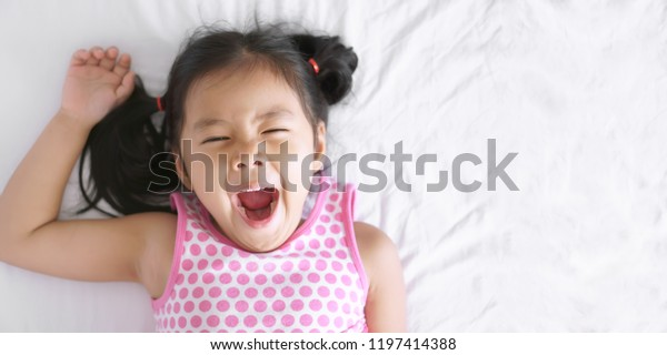 Asian child cute or kid girl sleep yawn and open mouth with stretch oneself after wake up late and sleepy in morning on white bed in bedroom for relax on holiday and wear pink dress with copy space