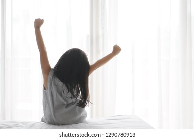 Asian child cute relax or kid girl wake up or woke up with stretch oneself after sleep for refreshing in morning on white bed and window with curtain in bedroom at home or hotel and resort on holiday
