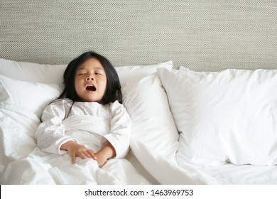 Asian child cute relax and yawn or kid girl sleep and wake up with stretch oneself and sleepy for refreshing in morning on white bed and pillow with blanket in bedroom at home or hotel on holiday