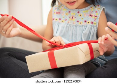 Asian Child daughter unwrapping gift box with her mom on bed in their bedroom togetherness.