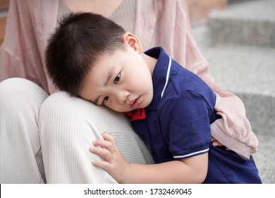 An Asian child depends on her mother's arms