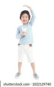 Asian child drinking milk from a glass and measuring himself  on white background isolated