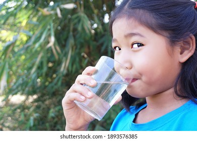 Asian Child drinking water in bottle outdoors with nature background.