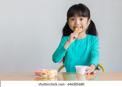 asian child eat ice cream and gummy jelly that are on the wooden table