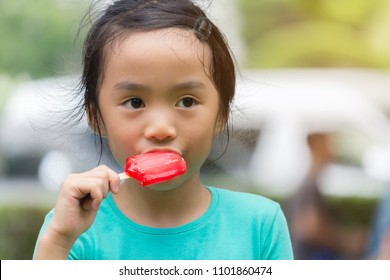 asian child eat red ice cream bar