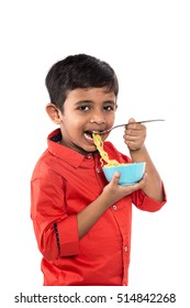 Asian child eating delicious noodle, Indian Kid eating noodles with Fork on White Background