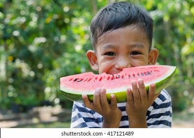 Asian Child Enjoy Eating The Watermelon.
