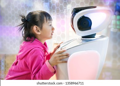asian child extends a hand to the robot. concept of friendship between the robot and child