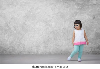 Asian child girl with concrete wall background in empty room