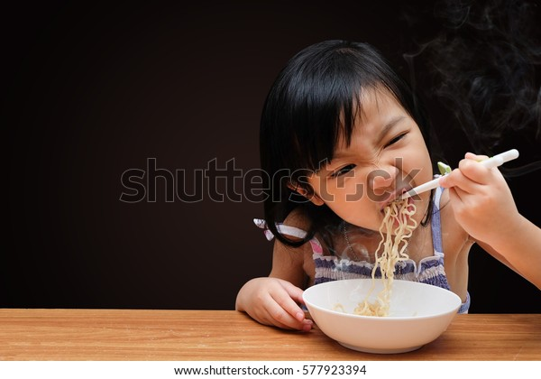 Asian child girl eating Instant noodles isolated on black background, with clipping path