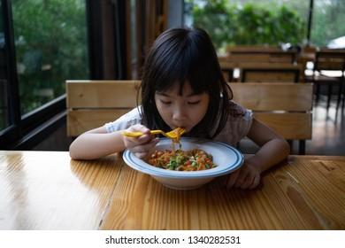 Asian child girl eating Spaghetti