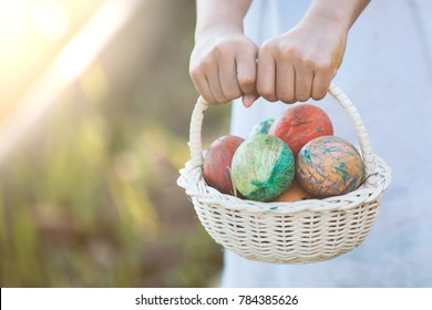 Asian child girl holding basket with colorful Easter eggs in outdoor