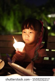 Asian child girl holding the candle in the dark.
