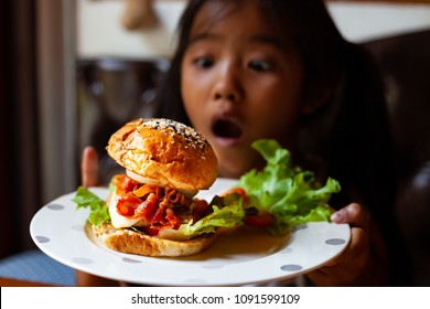 Asian child girl holding dish of delicious hamburger with excited to eat in the restaurant