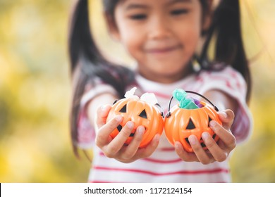 Asian child girl holding halloween bucket with sweet candy in hand for Halloween celebration