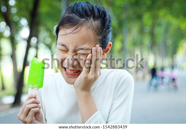 Asian child girl holding her hand on her aching tooth have hypersensitive teeth eating ice-cream,feel painful,female teenage have sensitive teeth problem with ice-lolly,tooth decay,dental care concept
