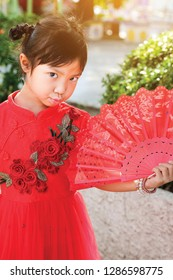 Asian child girl make puckering a facetious in red dress , Concept costume Chinese new year