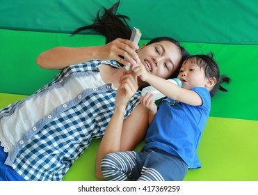 Asian Child girl and mother lying on the mattress and playing flash card for Right Brain Development at the playroom, Mother teaching her Child girl