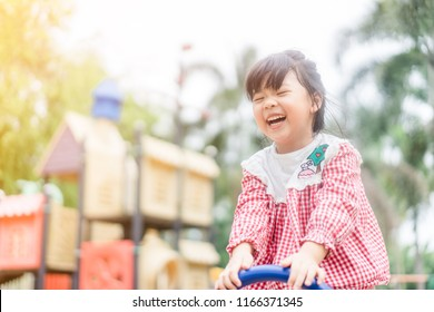 Asian child girl playing on playground in outdoor park.Happy Little asian girl playing seesaw with her mother.Happy moment and good emotion