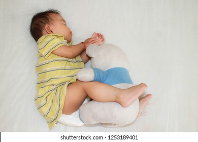 A asian child girl sleep on the bed and snuggle with a dirty bear doll in the bedroom.