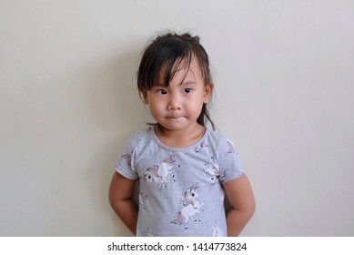 Asian child girl is standing absent-minded with isolated on white background.