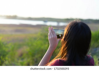 asian child girl Take pictures from the phone Happy fun Sunset view