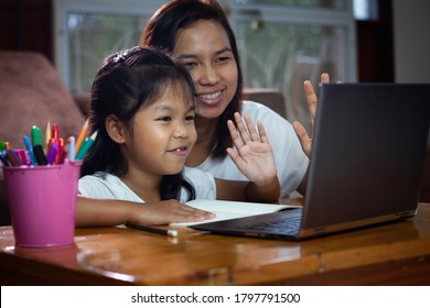 Asian child girl using notebook to learning online technology with her mother to advise beside. Concept of online education, social distance learning at home during quarantine and school holidays.