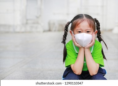 Asian child girl wearing a protection mask against PM 2.5 air pollution with pointing up in Bangkok city. Thailand.