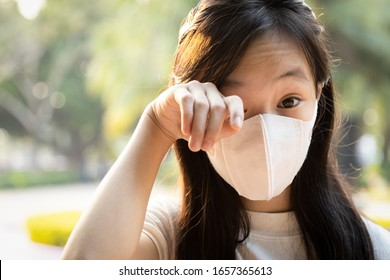 Asian child girl wearing protective medical mask,people with dirty hands,wash hands thoroughly before touching,rubbing the eyes,avoiding the infection from spread of Covid-19,prevent to Coronavirus