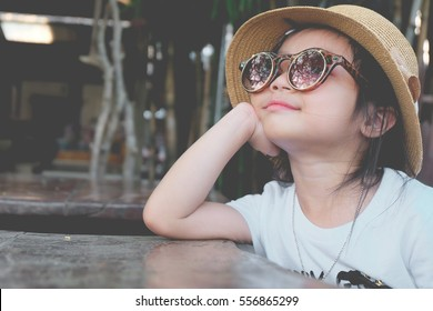 Asian child girl wearing sunglasses and a hat Pose hands chin