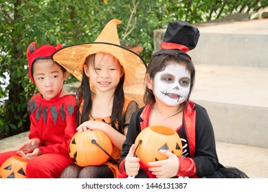 Asian child girls in halloween costumes with pumpkin sitting on the stairs at home