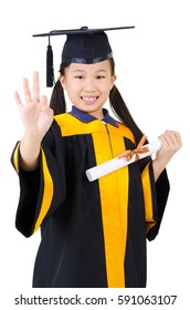 Asian child in graduation gown and mortarboard