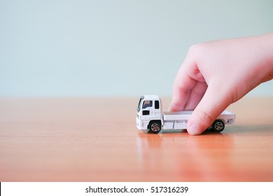 A asian child hand holding toy white car truck in hand on white background with copyspace, Learning and Education background concept