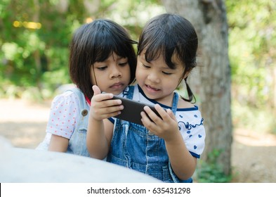 Asian Child Happy Play Tablet At Park